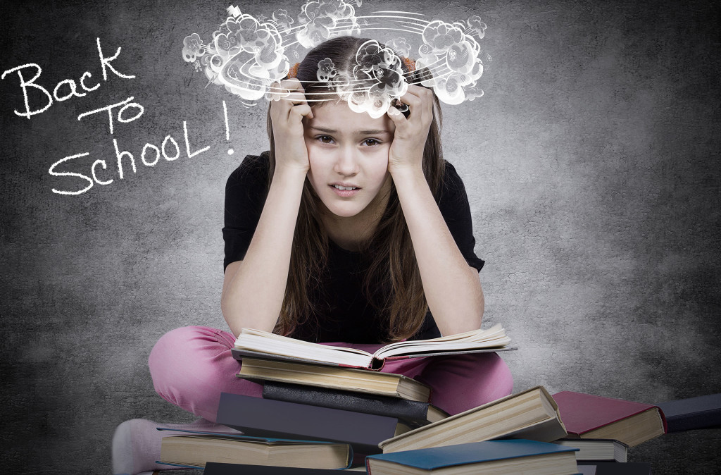 Closeup portrait young little girl, stressed tired fatigued upset, sitting on pile of books, isolated dark grey black background. Human emotion facial expression, reaction, feelings, education concept